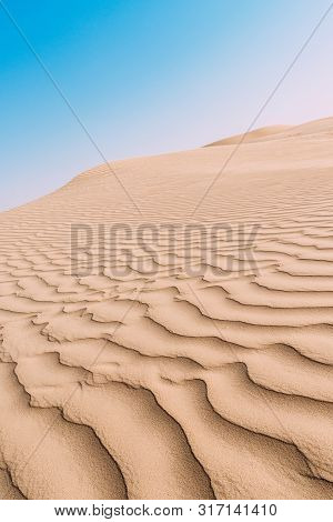 Close Up Top View Of Sand Dune Surface With Undulated Wave Patterns Former By Wind