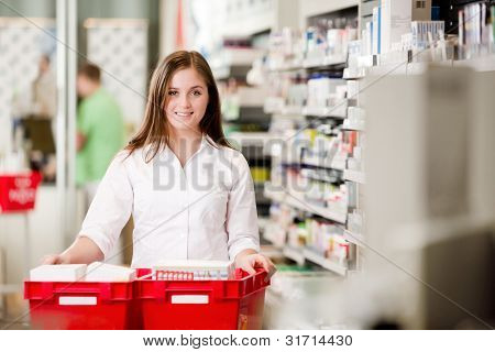 Attractive female pharmacist looking at camera in pharmacy setting.