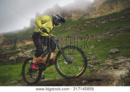 Side View Wide Angle Partly A Man On A Mountain Bike Travels On Rocky Terrain Against The Background