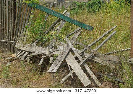 Gray Broken Wooden Plank Fence In Green Grass