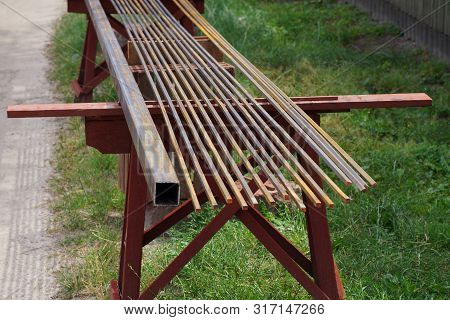 Row Of Iron Brown Rusty Reinforcement Rods In The Street On A Background Of Green Grass