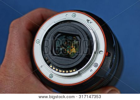 One Black Open Camera Lens In A Hand On A Blue Background