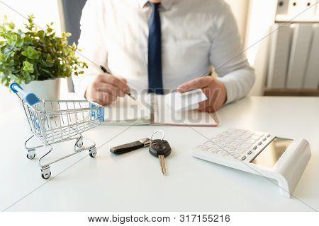 Businessman Calculating Shopping Expenses For Car Purchase, Holding Receipts In Hand. Empty Shopping