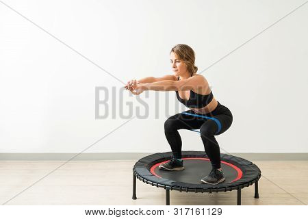 Confident Slim Female Doing Squats With Resistance Band On Trampoline During High Intensity Interval