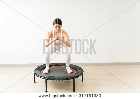 Confident Slim Fit Female Doing Squats On Mini Trampoline During High Intensity Interval Training At