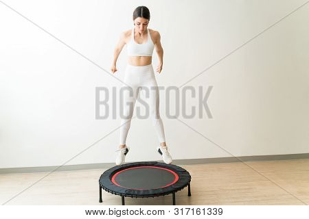Attractive Slim Caucasian Female Rebounding Against Wall During Interval Training At Fitness Studio