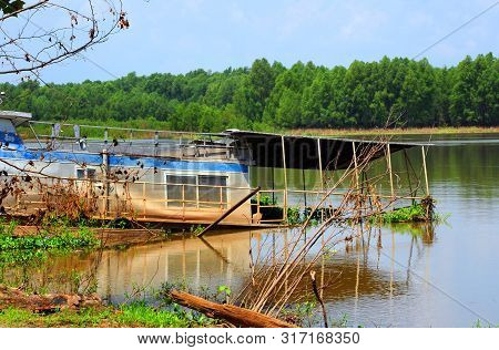 Long Houseboat Collapses As It Sit On The Arkansas River In Arkansas.  Muddy Water Has Stained Sides