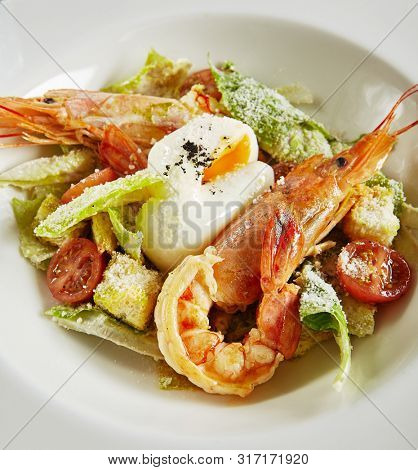 Exquisite Serving White Restaurant Plate of Caesar Salad with Shrimps, Chicken, Croutons, Tomatoes, Cucumbers Close Up. Beautiful Delicacy Seafood Cesar Salat on Black Marble Background poster