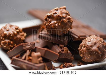 Chocolate Bar And Chocolate Ball On White Plate On The Dark Background / Chunks Candy Sweet Dessert