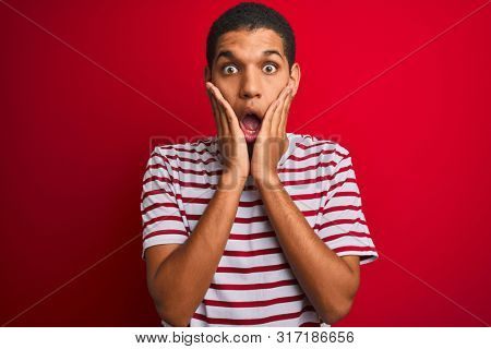Young handsome arab man wearing striped t-shirt over isolated red background afraid and shocked, surprise and amazed expression with hands on face