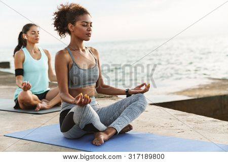 Two healthy fitness women doing yoga exercises on fitness mats at the beach, meditating