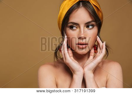 Close up beauty portrait of an attractive young topless woman wearing headband standing isolated over brown background, posing, touching her face, looking away