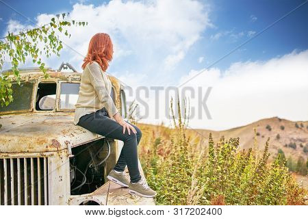 Woman Sitting On Rusty Old Classic Truck. Teenage Model Girl Posing In Sun Light On Autumn Field.