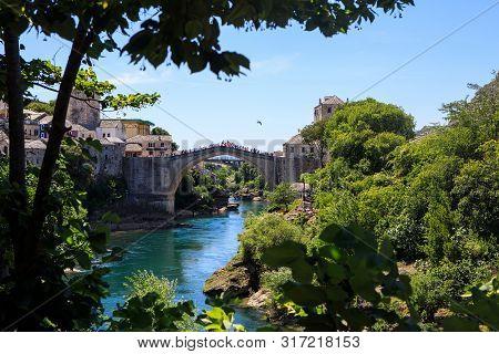 Mostar, Bosnia And Herzegovina - July 11, 2019: The Old Bridge In Mostar With Emerald River Neretva.