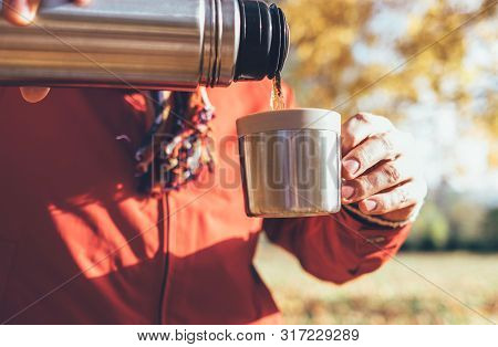 Young Male Hands Pouring A Hot Tea Into Cup   From Thermos Flask In Autumn Forest Close Up Image