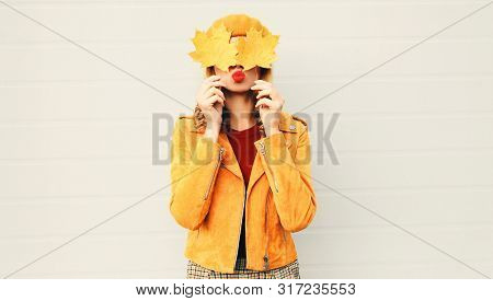 Autumn Mood! Woman Holding In Her Hands Yellow Maple Leaves Hiding Her Eyes Over Gray Wall Backgroun