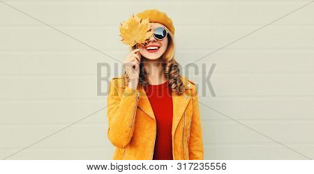 Autumn Mood! Happy Smiling Woman Holding In Her Hands Yellow Maple Leaves Hiding Her Eye Over Gray W