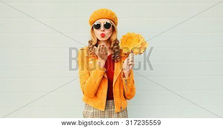 Autumn Portrait Woman With Yellow Maple Leaves Blowing Red Lips Sending Sweet Air Kiss Over Gray Wal