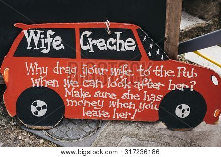 Lymington, Uk - July 14, 2019: Funny Wife Creche Sign On A Street Outside A Shop In Uk.