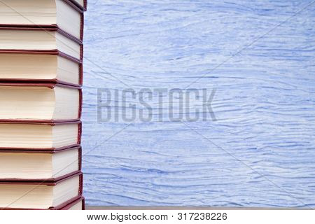 Stack Of Books On The Blue Background. Back To School. Education. Copy Space For Text.