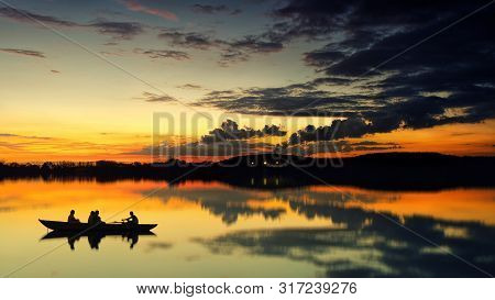 Silhouettes Of People On A Boat In The Lake On The Background Of A Picturesque Sunset.
