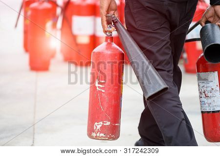 Closeup Of Fireman Lower Body Prepare To Fire Drill By Holding Portable Fire Extinguish And Water Ho