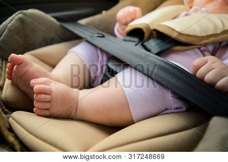 Safety Concept, Protection Of Child In Travel, Children Feet In Baby Seat. Small Newborn Baby Sittin