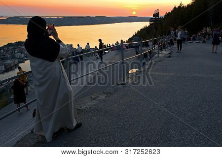 Bergen, Norway - July 26, 2019: Beautiful Landscape And Muslim Woman Taking Photo Of Sunset Seen Fro