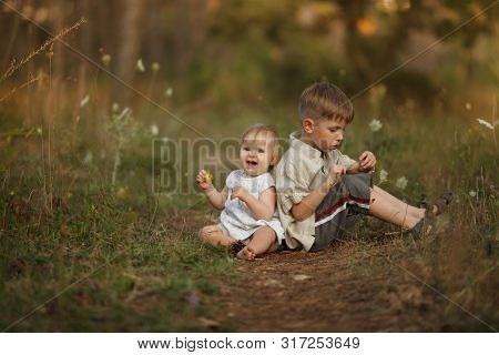Two Cute Happy Little Kids Sit Back To Each Other In Nature With Flowers. The Girl Smiles And Laughs