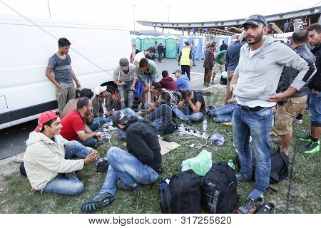 Bregana, Slovenia - September 19, 2015 : A Large Group Of Male Syrian Refugees Charging Their Mobile