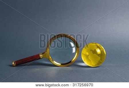 Magnifying Glass And Planet Earth Glass Ball. Concept Of Global Search And Globalization Process. In