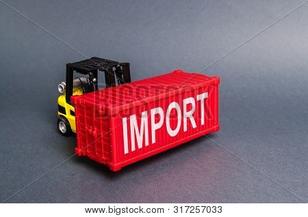 A Forklift Carries A Red Freight Container Labeled Import. The Concept Of Import Of Goods, Transport