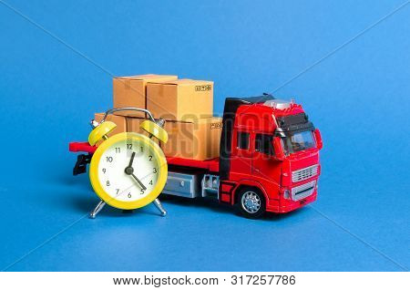 A Truck With Cargo Cardboard Boxes And A Yellow Alarm Clock. Express Delivery In Short Time Concept.