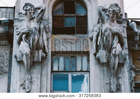 Two Statues Adorn The Facade Of An Old House