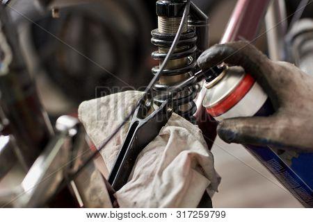 Cropped Shot Of Man Mechanic Working In Bicycle Repair Shop, Repairing Bike Using Special Tool, Wear