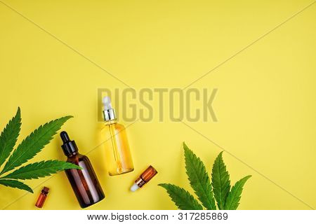 Bottles With Cbd Oil, A Dropper, And Leaf Marijuana On Yellow Background. Concept Beauty Care With H