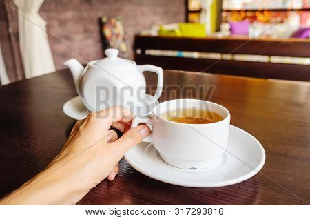 White Cup Of Tea And Teapot On A Table In A Cafe. Female Hand Holds A Cup. The Concept Of Tea Drinki