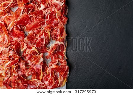 Appetizing Slices Iberian Ham In The Foreground. Olive Oil. Black Background. Space To Insert Your T