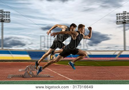 Man sprinter leaving starting blocks on the athletic track
