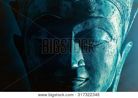 Spiriitual Enlightenment. Enlightened Buddha Face Statue Close-up. Bold Graphic Image With Atmosperi