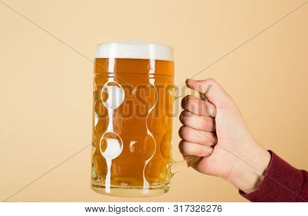 Beer In Mug With Foam. Fresh Cold Beer In Glass In Hand. Leisure, Drinks, Degustation, People And Ho