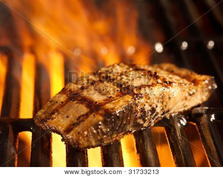 salmon fillet on the grill with flames in horizontal orientation