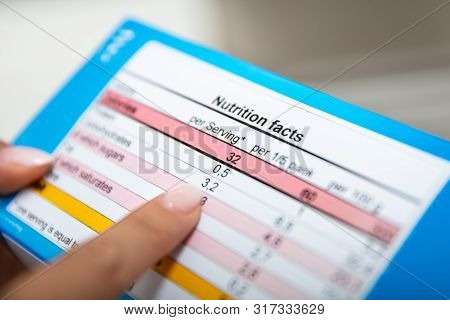 Close-up Of Woman Reading Nutrition Facts On Box