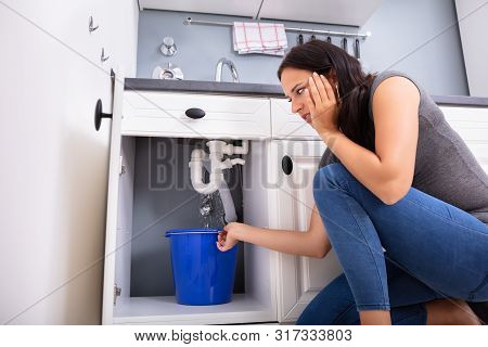 Young Woman Collecting Leakage Water In Bucket At Kitchen