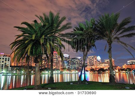 Coconut tree and Orlando downtown skyline over Lake Eola at dusk with urban skyscrapers and lights.