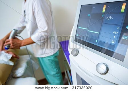 View Of Doctor Using Radial Shockwave Therapy Machine In Beauty Parlor