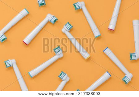 Pattern Of Electric Toothbrush Heads On An Orange Background