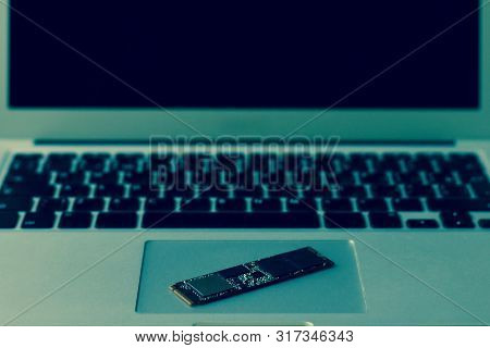 Ssd Drive Diagonally On The Trackpad. The Laptop Takes Up The Entire Frame Horizontally. Half Screen