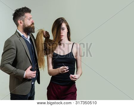 Beautify Your Hair Today. Bearded Hipster Holding Long Hair Of Pretty Woman And Hair Cutters. Profes