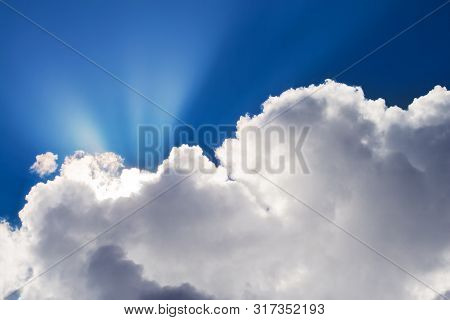 Big Puffy White Clouds Cover The Sun Creating Beautiful God Rays, Crepuscular Rays Against A Deep Bl